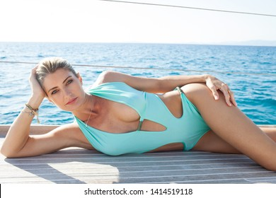 Beautiful sexy woman in swimwear on private luxury sailing yacht laying relaxing on deck, sunny outdoors. Beauty elegant female on exclusive summer vacation, leisure recreation aspirational lifestyle.
