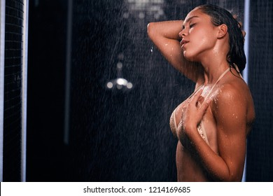 Beautiful sexy woman with tanned skin taking shower in spa bathroom. Portrait of fashion model girl indoors over black shimmering background.