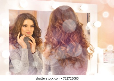 Beautiful sexy woman touching her face and looking at her reflection in the mirror.Woman with beautiful makeup and hair in curls.
