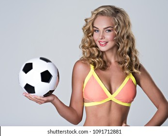 Beautiful sexy woman in trendy swimsuit holds a soccer ball. Attractive young girl with classic soccer ball on palm