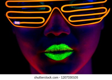 Beautiful sexy woman with UV face paint, glowing clothing, glowing bracelet in front of camera, face shot, cool look. Asian woman. Party concept.