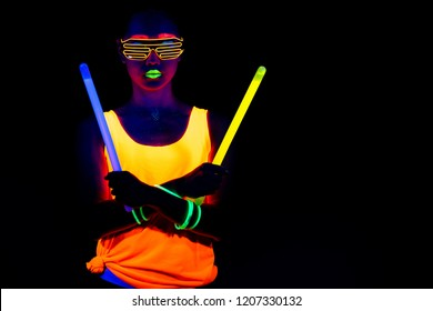 Beautiful sexy woman with UV face paint, glowing clothing, glowing bracelet in front of camera, half body shot, confident look, holding light sticks. Asian woman. Party concept.