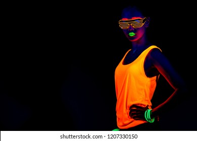 Beautiful sexy woman with UV face paint, glowing clothing, glowing bracelet in front of camera, half body shot, confident look. Asian woman. Party concept.