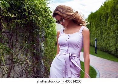 Beautiful sexy woman walk in the park summertime weather green trees road wear stylish short dress for party and walk glamour fashion clothes silk accessory bag outdoor street girl date perfect model