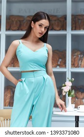 Beautiful sexy woman wear fashion summer collection clothes casual style dress slim body pretty face model pose accessory jewelry brunette hair bread shop cafe breakfast morning coffee blue suit.