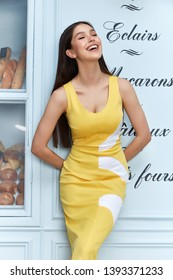 Beautiful sexy woman wear fashion summer collection clothes casual style yellow dress slim body pretty face model pose accessory jewelry brunette hair bread shop cafe breakfast morning coffee.