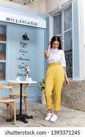 Beautiful sexy woman wear fashion summer collection clothes casual style blouse yellow trousers slim body pretty face model accessory jewelry brunette hair bread shop cafe breakfast morning coffee.