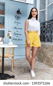 Beautiful sexy woman wear fashion summer collection clothes casual style slim body pretty face model pose accessory jewelry brunette hair bread shop cafe breakfast morning coffee blouse yellow short.