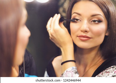 Beautiful sexy woman wearing makeup looking in the mirror