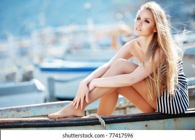 Beautiful sexy woman wearing sailor striped dress posing in boat