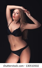 Beautiful and sexy woman wearing sensual lingerie on black background in studio
