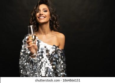 Schöne, sexy Frau mit glänzendem Kleid mit Glas Champagner auf schwarzem Hintergrund.