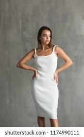Beautiful sexy woman in white skin-tight dress.