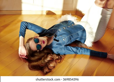 Beautiful sexy woman white skirt slinky dress blue denim jacket feathers fashion stylish trend collection catalog spring summer clothing lying floor of wooden flooring in sun glasses style accessories