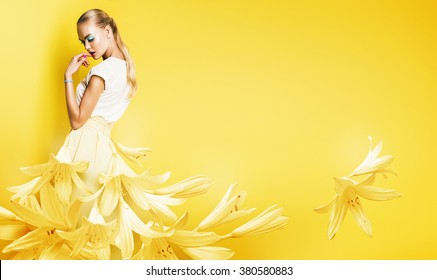 beautiful sexy woman in yellow flower dress on yellow background