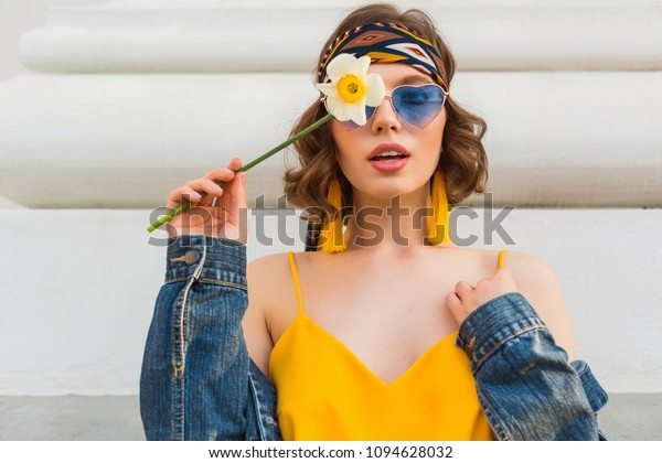 beautiful sexy woman in yellow stylish dress wearing denim jacket, holding flower, trendy outfit, hippie indie style, spring summer fashion trend, blue sunglasses, street fashion, trendy accessories