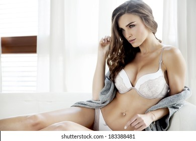 Beautiful and sexy young adult sensuality brunette woman in white lingerie and grey sweater on the white sofa in window on luxury apartment