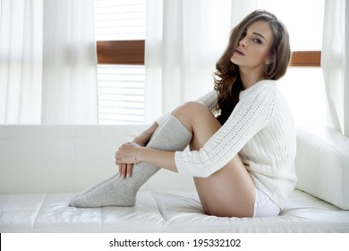 Beautiful and sexy young adult sensuality brunette woman in white sweater and grey socks on the white sofa in window on luxury apartment