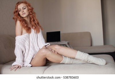 Beautiful and sexy young adult sensuality red hair woman in white sweater and grey socks on the white sofa in window on luxury apartment