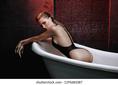 beautiful sexy young blond woman in bath with rose petals