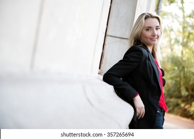 Beautiful sexy young blond woman posing against the wall of the building