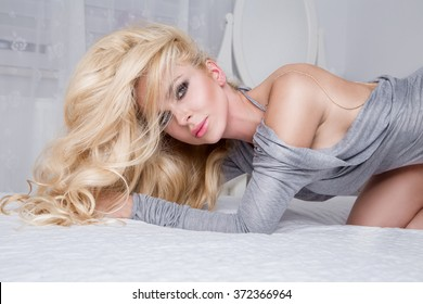 Beautiful sexy young blonde model with long curly hair lying in the bedroom on the bed of the senses in a gray dress with open back, with a big neck back and looks at the camera sensually