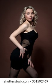 Beautiful sexy young blonde woman in a short black dress posing on a brown background