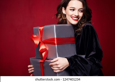 Beautiful sexy young brunette girl with wavy hair bright evening make-up red lips long fluffy eyelashes hold gift box holiday New Year  joy fun happy merry Christmas Eve party celebration.