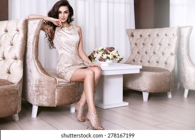 Beautiful sexy young brunette woman with long wavy hair thin slender figure perfect body and pretty face make-up wearing a beige evening skinny dress and jewelry