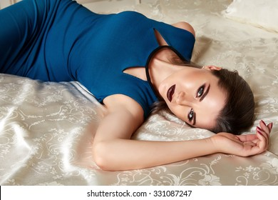 Beautiful sexy young brunette woman with long hair thin slender figure perfect body and pretty face makeup wearing blue slim fit silk dress small bag high heels gold interior luxury furniture bed room