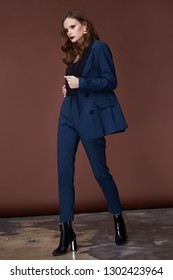 Beautiful sexy young business woman dark hair evening makeup wearing formal suit jacket pants high heels shoes business clothes for meetings walks autumn spring collection perfect body shape make-up.