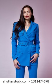 Beautiful sexy young business woman brunette hair evening makeup wearing dress blue suit jacket trousers high heels shoes business clothes for meetings walks fall collection perfect body shape.