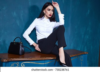 Beautiful sexy young business woman brunette hair luxury chic wear casual style for office white blouse trousers black pretty face  autumn collection glamor model fashion clothes interior room bag.
