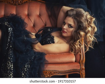 beautiful sexy young charming blonde girl is lying on the sofa in a vintage studio room, the model is dressed in a stylish retro dress from the collection, elegant hairstyle, makeup, close-up, portrai