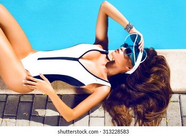 Beautiful sexy young girl with perfect slim figure with long wet hair and bathing suit in fashionable stylish sun glasses sitting on the steps of swimming pool swim, sunbathe, have fun at beach party