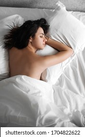 beautiful sexy young girl sleeping on a pillow under a white blanket on the bed in the morning