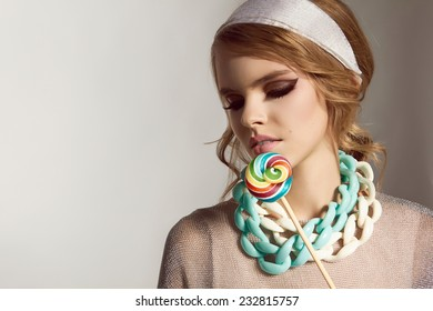 Beautiful sexy young girl with wavy blond hair and silk scarves, soft natural make-up in a shiny silver jacket, blue and white necklace around the neck in the form of a chain, candy on a stick caramel