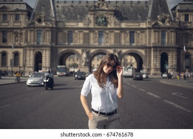 Beautiful and sexy young lady with long hairs and sunglasses stands in the middle of the bridge in Paris, France.