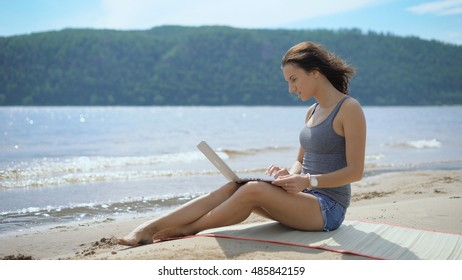 A beautiful sexy young lady is sitting at a beach using laptop enjoying the beautiful view. Freelance work in front of the sea.