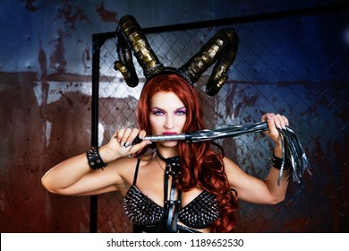 beautiful sexy young model wearing Halloween costume ,leather and horns standing behind the chain link fence