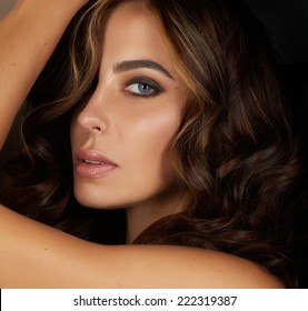 Beautiful sexy young woman with blue eyes plump lips, evening make up and black eyelashes dyed brunette with curly or wave hair on her shoulder with golden Tan skin looks into the camera from her back