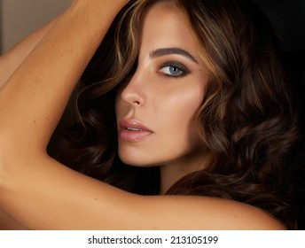 Beautiful sexy young woman evening make up dark eye eyelashes dyed brunette waves stacked hair nude shoulder Golden Tan looks into the camera from the back