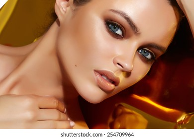 Beautiful sexy young woman evening make up dark eye eyelashes dyed brunette waves stacked hair nude shoulder Golden Tan looks into the camera makeup artist cosmetic beauty salon spa