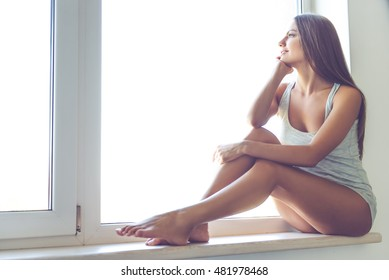 Beautiful sexy young woman in gray singlet is looking out the window, dreaming and smiling while sitting on the window sill at home