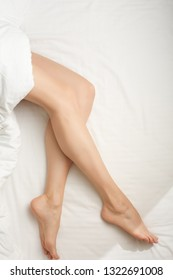 beautiful sexy young woman legs on the white sheets. Naked female legs is lying on bed covered by blanket.