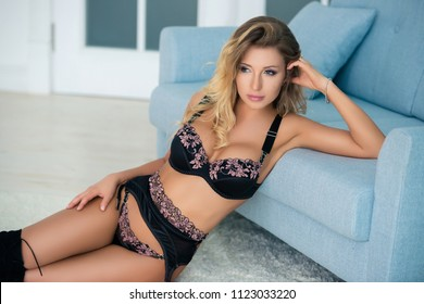 Beautiful sexy young woman in lingerie sitting on the floor.