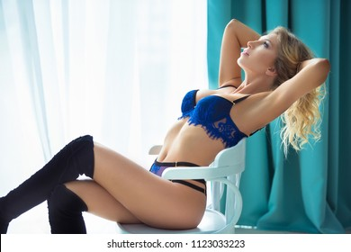Beautiful sexy young woman in lingerie sitting on a chair