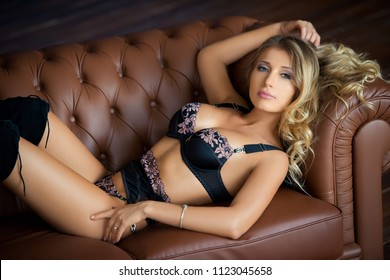 Beautiful sexy young woman in lingerie lying on the couch