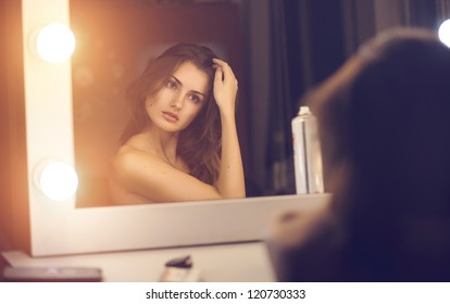 Beautiful sexy young woman looking into a mirror at herself