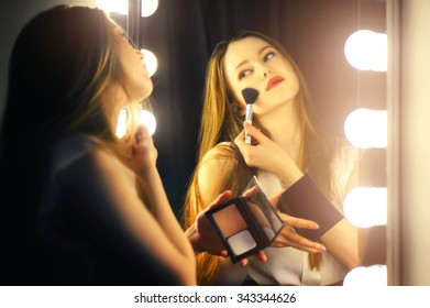 Beautiful sexy young woman looking into a mirror at herself and use cosmetic brush powder on her face.